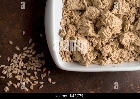 Pieces of halva in a bowl, seeds on a metal table horizontal - Stock Photo