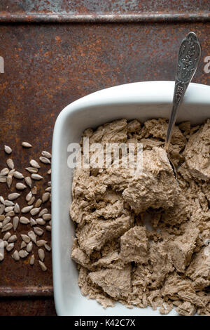 Pieces of halva in a bowl, spoon and seeds on a metal table vertical - Stock Photo