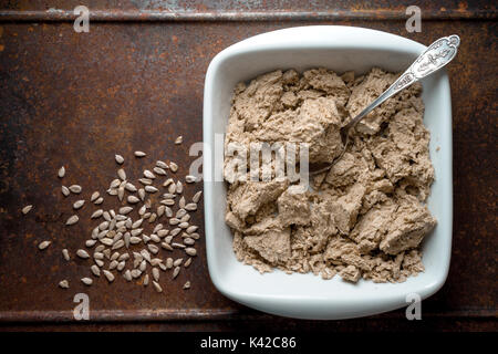 Pieces of halva in a bowl, spoon and seeds on a metal table top view horizontal - Stock Photo