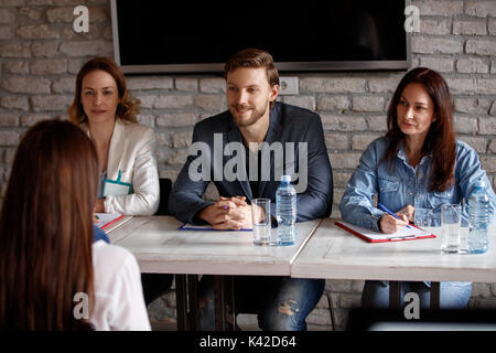 Members of company commission interviewing candidate - Stock Photo