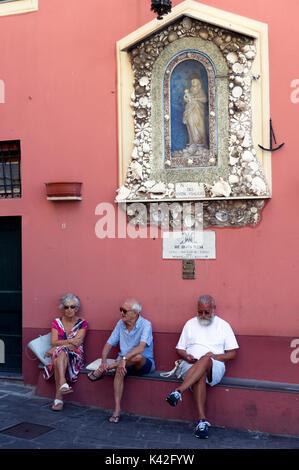 Italy. Liguria. The fishing village of Camogli. Elderly people relaxing in Camogli - Stock Photo