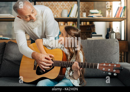 Loving grandfather teaching his granddaughter how to play guitar - Stock Photo