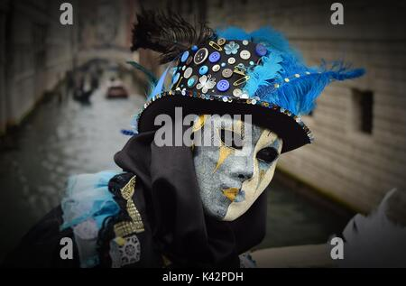 A person in costume at the Carnival of Venice, wearing a black hat decorated with buttons, safety pins and blue - Stock Photo