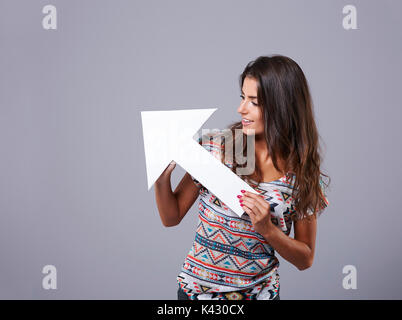 White arrow sign held by attractive young woman - Stock Photo
