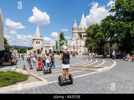 Tourists exploring the The iconic Fisherman's Bastion riding Segways, Castle District, Buda, Budapest, capital city - Stock Photo