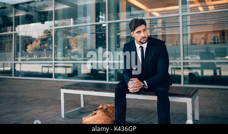 Businessman sitting on bench with handbag and looking away. Business traveler waiting outside airport. - Stock Photo