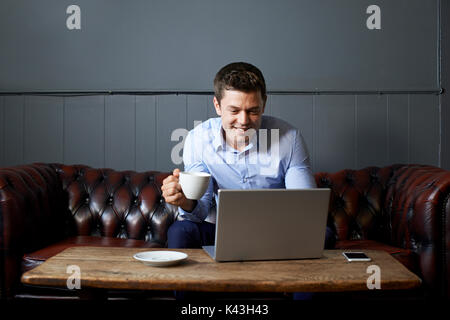 Businessman Drinking Coffee Whilst Working On Laptop In Internet Cafe - Stock Photo