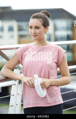 Young Woman Resting On City Bridge During Exercise - Stock Photo