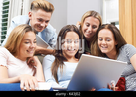 Group Of Teenagers Using Digital Technology At Home - Stock Photo