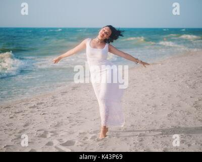 The young girl enjoys good windy weather on sea beach. Woman is dressed in white sundress and boho jewelry rest - Stock Photo