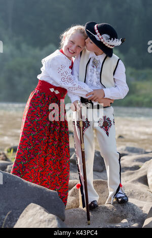 Siblings, brother spontaneously kissing smiling sister. Children wearing traditional Polish mountain people clothes - Stock Photo