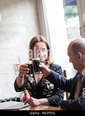 Professional real people, young adult woman, senior man, having informal business meeting in pub at glass of dark - Stock Photo