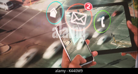 Close up of hands using digital tablet and mobile phone against blurred motion of vehicles on road - Stock Photo
