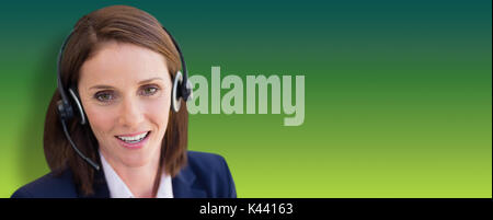 Close-up of smiling woman talking on microphone headset against green abstract background - Stock Photo