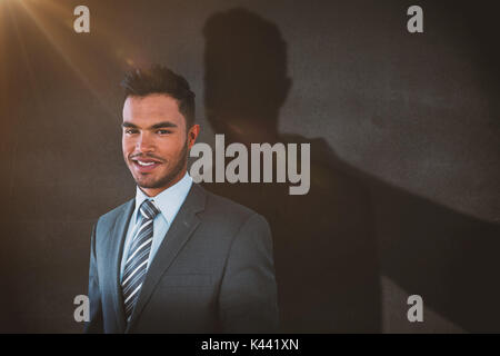 Smiling businessman standing against white background against black wall - Stock Photo