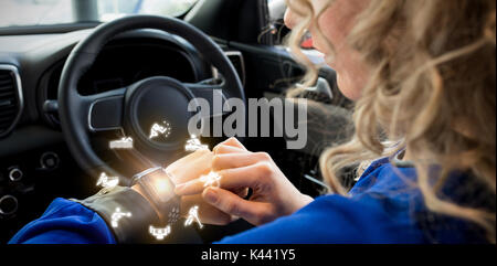 Graphic image of various sports activities against close up of woman using smart watch in car - Stock Photo