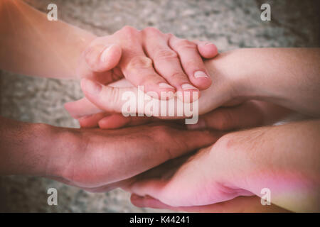 Cropped image of people forming hands stack against texture of cracked earth - Stock Photo