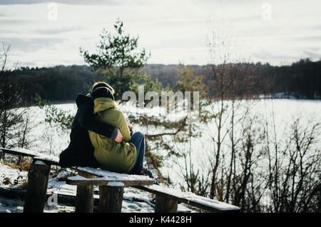 Joyful cute couple in warm clothes embraces. Young man hugs a girl. Couple sit on wooden bench in winter and look - Stock Photo