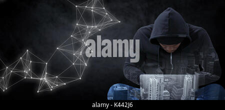 Male hacker using laptop while sitting against black - Stock Photo
