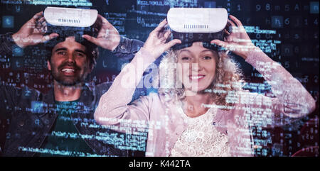 Image of data against couple using virtual reality headset - Stock Photo