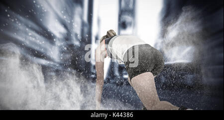 Female athlete in position ready to run against splashing of dust powder - Stock Photo