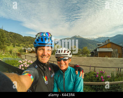 Cycling Mountains Alps Couple Cyclists Selfie Bike riding bikewear cycle helmets on sunglasses panoramic landscape - Stock Photo