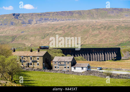 Station Inn pub and Bunk Barn with diesel train crossing Ribblehead viaduct below Whernside. Yorkshire Dales National - Stock Photo