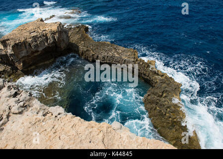 Rocky coastline and sea. Blue hole and the collapsed Azure window in Dwejra Bay, Gozo, Malta - Stock Photo