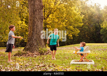 two boys playing jump rope with their baby brother - Stock Photo