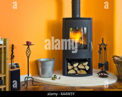 A modern wood burning stove, alight, in front of a vibrant orange wall in a living room in a  contemporary  British - Stock Photo