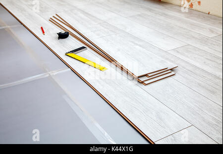 laminate boards prepared for laying on the floor in the room closeup - Stock Photo
