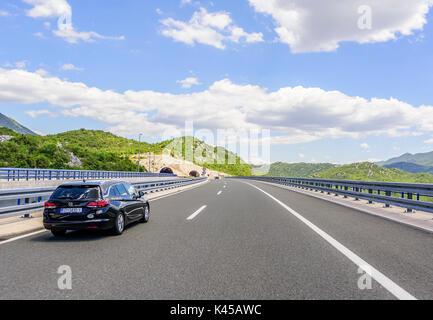 MAKARSKA, CROATIA - JULY 16, 2017: Cars speeding on the Autobahn among mountain scenery. - Stock Photo