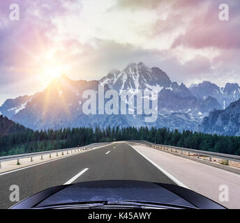 Cars speeding on the Autobahn among mountain scenery. - Stock Photo