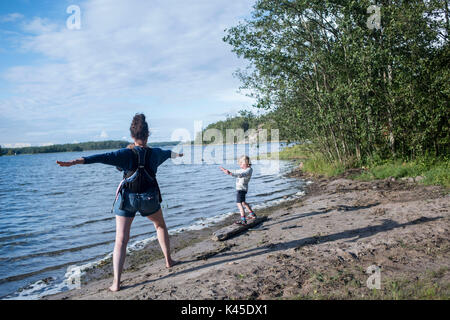 Finland mother and son doing sun salutations island of Hogsara south Finland Archipelago National Park on the shores - Stock Photo