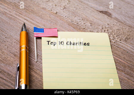 Charity and Donation concept on notebook and wooden board - Stock Photo