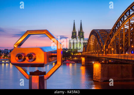 Hohenzoller Bridge over River Rhine and Cologne Cathedral with binoculars at dusk in Cologne city. Cologne city - Stock Photo