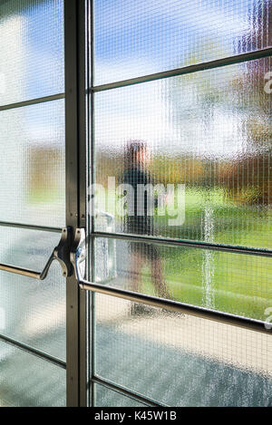 View through glass door of mid adult woman squirting cleaning usa new york hudson valley beacon view through frosted door glass planetlyrics Gallery