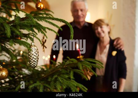 Senior couple in front of Christmas tree, half portrait - Stock Photo