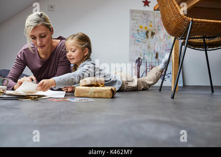 Mother and daughter writing Christmas cards - Stock Photo