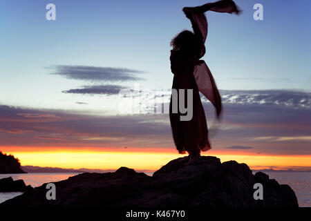 Artistic dynamic photograph of a woman back dark silhouette in long red dress dancing on the rocks of an ocean shore - Stock Photo