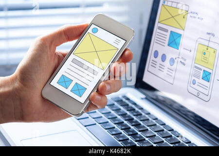 Mobile responsive website development with UI/UX front end designer previewing wireframe sketch layout design mockup - Stock Photo