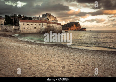 European tourist resort sea fort Budva with medieval architecture at sunset beach with dramatic sky in Europe country - Stock Photo