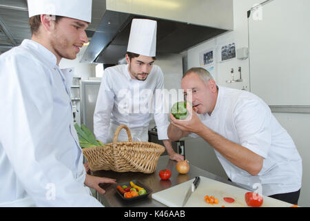 butcher teaching apprentice how to prepare meat - Stock Photo
