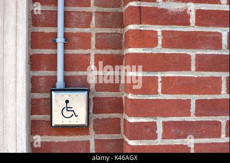 Handicap activated door opener on red brick wall - Stock Photo