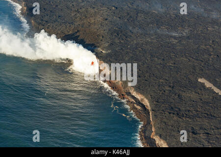 Aerial view showing how far the cloud of steam caused by the active volcano red lava flow extends - Stock Photo