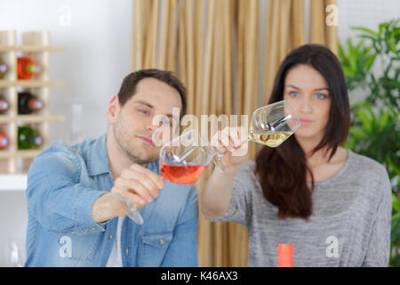 young winery employees checking up quality of wine in glass - Stock Photo