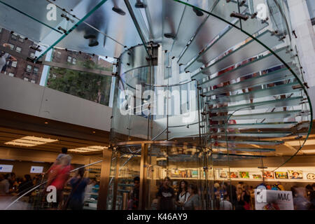 Tourists in the famous glass stairs of the the cube, Apple Store in 5th avenue, Manhattan, New York City. - Stock Photo