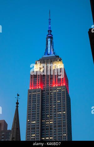 Empire State Building at night showing the colors of the American flag, red, white and blue - Stock Photo