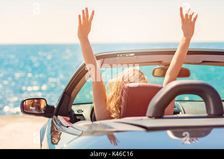 Happy and carefree woman in the car on the beach - Stock Photo