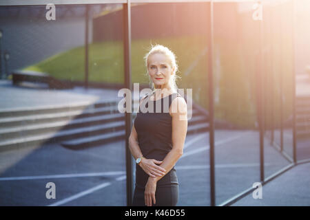 Portait of mature businesswoman standing in front of modern glass building. - Stock Photo